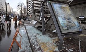 Japan Tsunami: People walk by a bus stop which was destroyed in Sendai, Miyagi prefecture