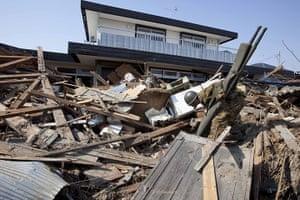 Dan Chung in Japan: A rescue worker picks through the ruins in Shintona, Japan