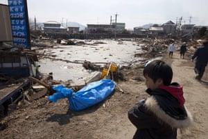 Dan Chung in Japan: A boy stands near a body bag o the street in Shintona, Japan