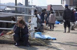 Dan Chung in Japan: A woman grieves amongst the tsunami damage in Shintona, Japan