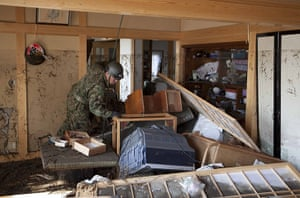 Dan Chung in Japan: A rescue worker examines the interior of a house