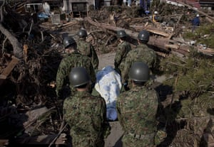 Dan Chung in Japan: Rescue workers carry away a body