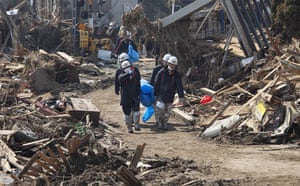 Dan Chung in Japan: Rescue workers carry a body bag through destruction