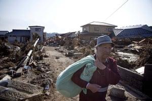 dan chung in Shintona: A man walks through an area severley damaged