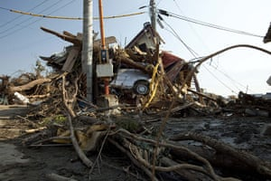 dan chung in Shintona: A car is buried amongst the remains of a house