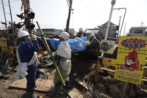 Dan Chung in Japan: Rescue workers remove a body