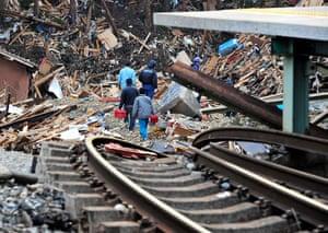 Japan rescue work: Local villagers make their way along twisted train tracks in Kesennuma