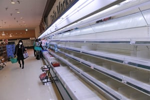 Japan rescue work: A woman walks past empty shelves at a supermarket in Akita