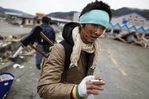 Japan rescue work: An injured survivor searches for food at a destroyed supermarket