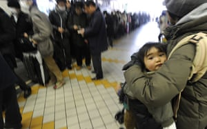 Japan rescue work: A woman holds a child in a long queue to get out of the city of Yamagata,