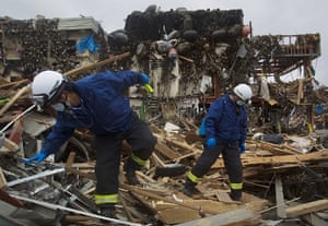 Japan rescue work: Japanese recovery officials search through the ruins of Minamisanriku