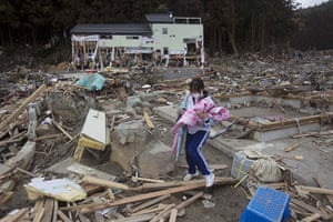 Japan rescue work: A survivor searches her family home for any belongings in Minamisanriku