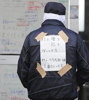 Japan rescue work: An evacuee, with a note of  family names, at a shelter in Ishinomaki