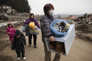 Japan rescue work: The Sasaki family carry some of their personal belongings in Rikuzentakata