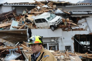 Japan rescue work: A rescue worker takes a break while searching for survivors in Ofunato