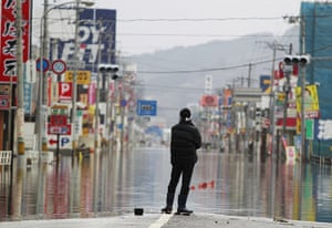 Japan rescue work: A man stands on a flooded street in Ishinomaki