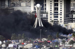 Bahrain uprising: Black smoke billows from burning tents in Pearl Square in Manama