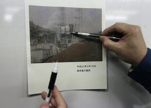 japan disatster: Tokyo Electric Co. employees with a photo of the Fukushima Dai-ichi complex