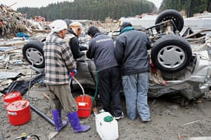 japan disatster: People siphon petrol from a car in Minamisanrikucho in Miyagi Prefecture