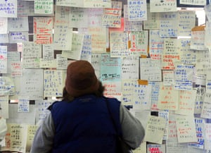 japan disatster: A woman checks notices left for loved ones in Natori