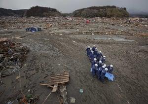 japan disatster: Policemen carry the bodies of  victims in Rikuzentakata