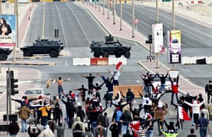 Bahrain uprising: Anti-government protesters wave in front of military vehicles