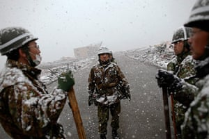 Japan aftermath: An army officer instructs his team in the residential area of Otsuchi as heavy snow falls