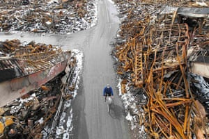 Japan aftermath: A man rides a bicycle at an area hit by earthquake and tsunami in Kesennuma