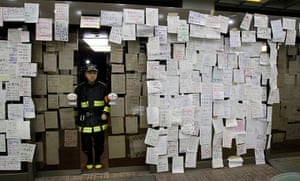 Japan aftermath: Survivors' notes seeking information about missing relatives and friends hang on the entrance of Natori city hall
