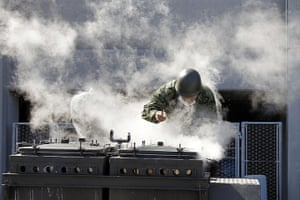 Japan aftermath: An army officer cooks steamed rice to distribute to evacuees in Koriyama