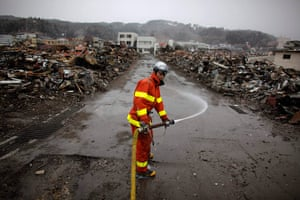 Japan aftermath: A fireflighter sprays water to clean a street in the debris in Yamada