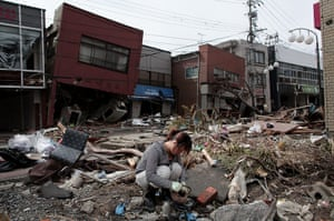 Japan aftermath: A woman sifts through the rubble of her home in Kesennuma