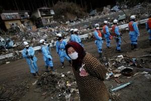Japan aftermath: A woman walks through a residential area in Rikuzentakata