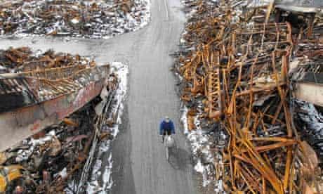 A man rides a bicycle at an area hit by earthquake and tsunami in Kesennuma, Japan