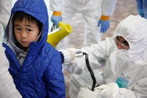Japan aftermath: Medical staff in protective gear checking radiation levels in Koriyama