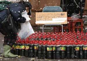 Japan aftermath: A woman picks up a bottle of soy sauce at Kamaishi city, Japan