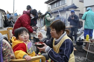 Japan aftermath: Survivors eat food they cooked on a road blocked in Ishinomaki