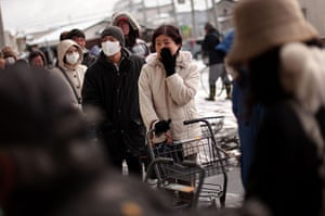 Japan aftermath: A woman waits in a line outside a grocery store in Ichinoseki