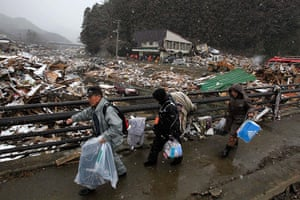 Japan aftermath: People walk from their damaged house in Kamaishi, Japan
