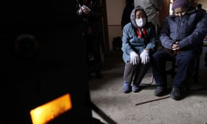 An couple sit near a stove in gymnasium being used to house those displaced in town of Otsuchi