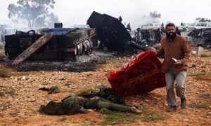 A Libyan man carries a blanket to cover the body of a loyalist soldier near Benghazi