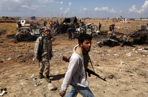 Libya airstrikes: Libyan rebels walk past wrecked military vehicles in Al-Wayfiyah