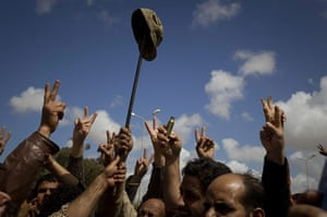 Libya airstrikes: Libyan rebels celebrate with a soldier's army cap