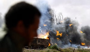 Libya airstrikes: A rebel fighter looks at burning vehicles after an air strike