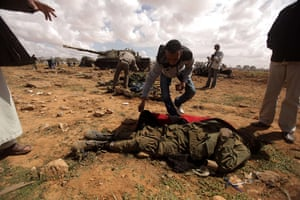 Libya airstrikes: A Libyan rebel empties the pockets of a member of Muammar Gaddafi's forces