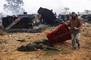 Libya airstrikes: A Libyan man carries a blanket to cover the body of a loyalist soldier