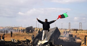 Libya airstrikes: A Libyan rebel waves a flag as he stands on wrecked military vehicles