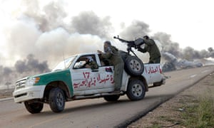 Libya airstrikes: Libyan rebel soldiers drive by burning vehicles hit by coalition forces