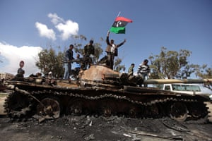 Libya airstrikes: Libyan rebels wave their flag on top of a wrecked tank near Benghazi