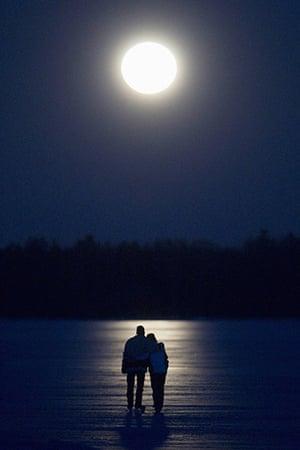 Super moon: A couple skate under a full moon on Pigeon Lake near Bobcayeon, Ontario